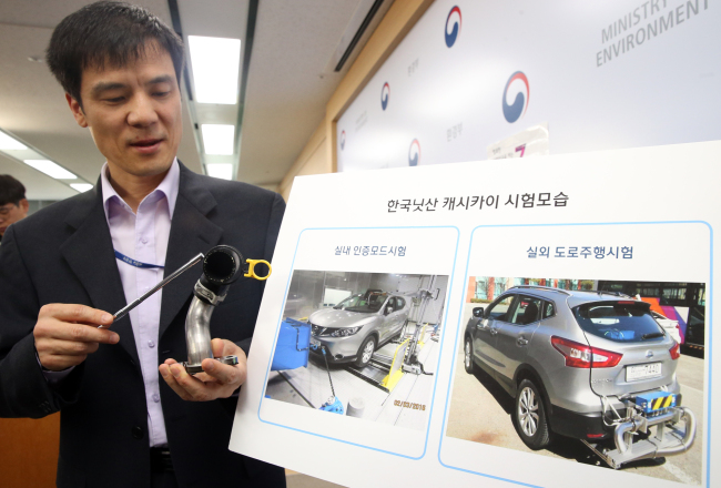 An Environment Ministry official demonstrates the exhaust gas recirculation system of Nissan's Qashqai model during a press conference Monday. (Yonhap)