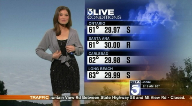 A screen capture of a KTLA-TV weather forecast where weather anchor Liberte Chan puts on a gray sweater handed over by cohost Chirs Burrous from off camera. (KTLA)