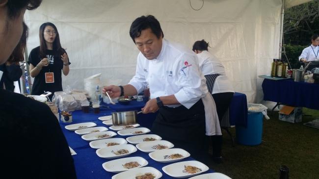 Chef Ming Tsai prepares a main dish of Amberjack sashimi, Madras curry oil and unistuffed pyogo mushroom at his tent. (Kim Hoo-ran/ The Korea Herald)
