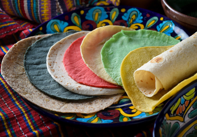 A colorful assortment of tortillas offered locally. From left, Whole Wheat flour (LaTapatia), Blue Corn (Vallaria), small flour fajita (Sol de Oro), Red Chile corn (Vallaria), white corn (Vallaria), Cactus corn (Vallaria), yellow corn (Mission), and large flour (LaTapatia). (Fresno Bee/TNS)