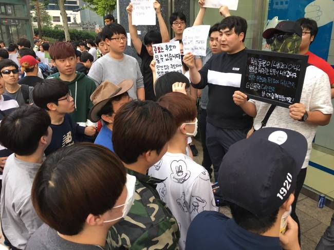 "Pro-men activists hold up placards reading, ""Not all meat eaters are bad, but only animals committing crimes are bad"" and ""Hatred cannot be mourning. Let's make prejudice-free Korea"" outside exit 10 of Gangnam Station on Sunday. (Ock Hyun-ju/The Korea Herald)"