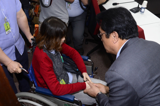Saenuri Party floor leader Chung Jin-suk greets a humidifier sterilizer victim at the National Assembly on Tuesday. Park Hae-mook/The Korea Herald