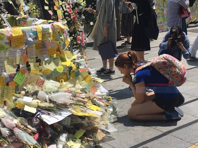 A foreign woman prays in front of post-it memos outside exit 10 of Gangnam Station on Sunday. (Ock Hyun-ju/The Korea Herald)