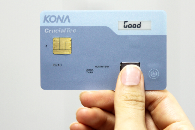 Fingerprint module maker CrucialTec and smart card firm Kona-I roll out a credit card installed with a fingerprint sensor in Seoul on Wednesday. (CrucialTec)
