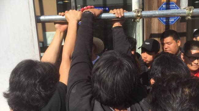 Old residents block yongyeok ggangpae -- criminal gangs who disguise themselves as legitimate business and are often mobilized to forcibly remove residents for demolition --whenthe court ordered to execute the evacuation process on May 17. (Okbaraji Preservation Committee)