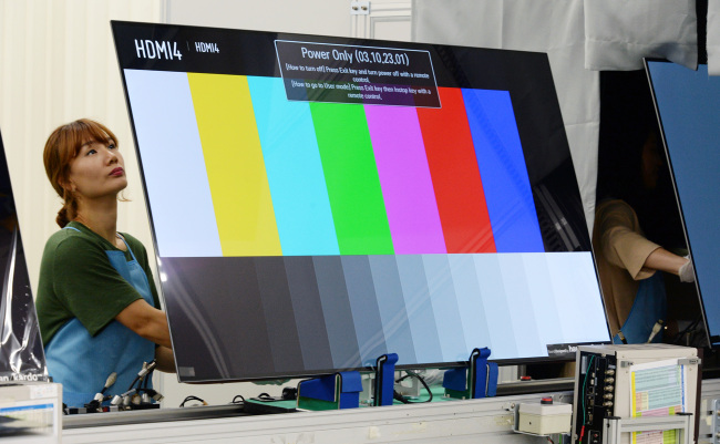 Workers monitor the organic light-emitting diode TVs along an assembly line at LG Electronics' A3 factory in Gumi City, North Gyeongssang Province on Friday. (LGE)