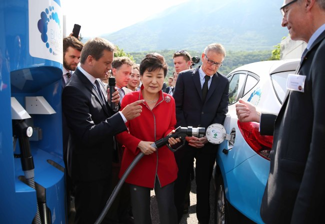 South Korean President Park Geun-hye (center) fuels hydrogen gas into Hyundai Motor's Tucson Fuel Cell vehicle during her visit to a research facility operated by French industrial gas supplier Air Liquide in Grenoble, France on Saturday. (Yonhap)