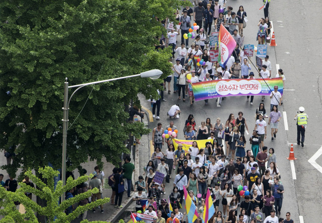 Participants march through central Seoul at the Pride Parade, waving rainbow-colored fans and flags, Saturday. (Yonhap)