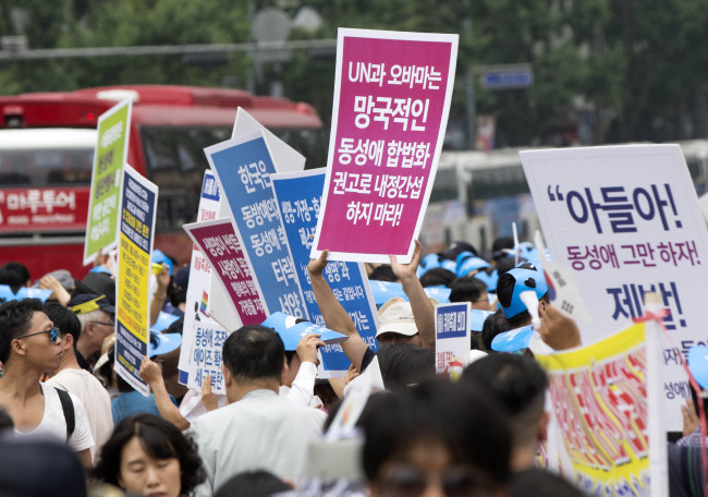 "Anti-homosexuality protestors hold up placards reading ""The United Nations and U.S. President Barack Obama must stop intervening in the country's affairs through ruinous recommendations for a legalization of homosexuality"" or ""Encouraging homosexuality spreads aids and increases taxes."" (Yonhap)"