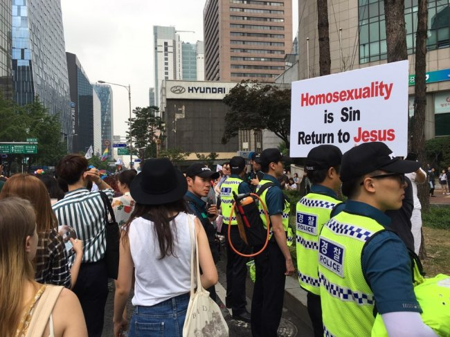 An anti-homosexuality protestors hold up a placard reading
