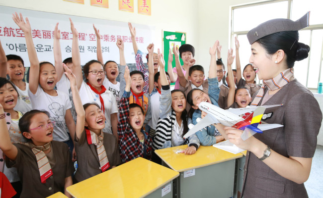 An Asiana Airline cabin crew member interacts with students at Xintan Elementary School in Jiangsu province, China, Tuesday. Asiana Airlines donated eight computers, 400 desks and 1,000 books to the school as part of its 25th Beautiful Classroom partnership. The Beautiful Classroom project is Asiana Airlines' global corporate social responsibility program, sponsoring schools in China since 2012. Pictured: (Asiana Airlines)