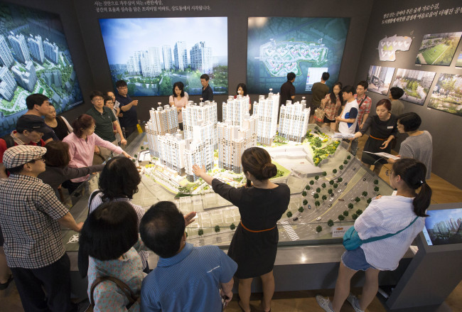 Visitors listen to the explanation of an apartment complex development near Sangdo Station in southern Seoul on Sunday. (Yonhap)