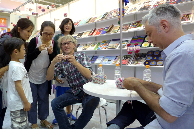 Norwegian and Swedish knitwear designers Arne Nerjordet (center) and Carlos Zachrison (right) demonstrate knitting in front of Korean audiences at the Seoul International Book Fair 2016 at Coex in Seoul. (Joel Lee / The Korea Herald)