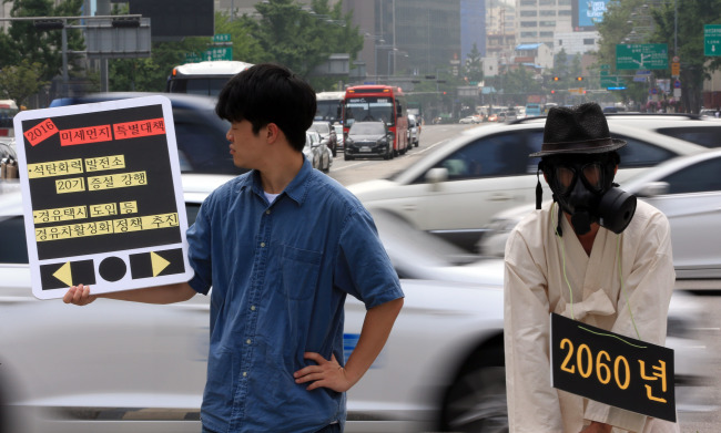 Members of Korea Federation for Environmental Movements hold a performance calling for fundamental measures to tackle fine dust problem at Gwanghwamun in Seoul on June 13. (Yonhap)