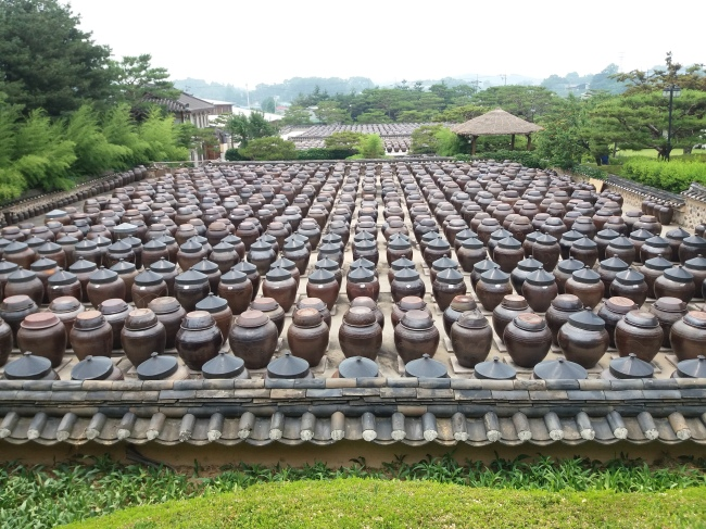 Porous onggi clay pots are filled with jang fermenting in the sun. (Christine Cho)
