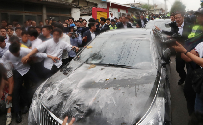 Prime Minister Hwang Kyo-ahn attempts to get through angry crowds in a car in Seongju on Friday. (Yonhap)