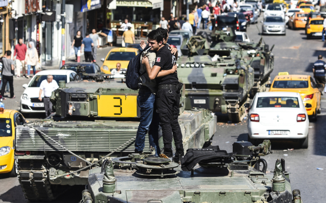 Turkish police officer (R) embrace a man on a tank after the military position was taken over at the Anatolian side at Uskudar in Istanbul on Saturday.President Recep Tayyip Erdogan urged Turks to remain on the streets on July 16, 2016, as his forces regained control after a spectacular coup bid by discontented soldiers that claimed more than 250 lives. Describing the attempted coup as a