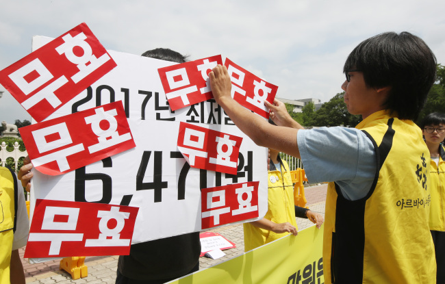 Members of a union for part-timers stage a performance protesting the minimum wage for 2017 in front of the National Assembly on Monday. (Yonhap)