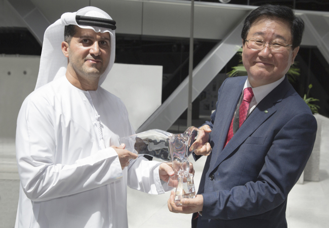 KHNP president Cho Seok (right) and UAE ENEC CEO Mohamed Al Hammadi exchange gifts after reaching a nuclear reactor deal in UAE last week. (Yonhap)