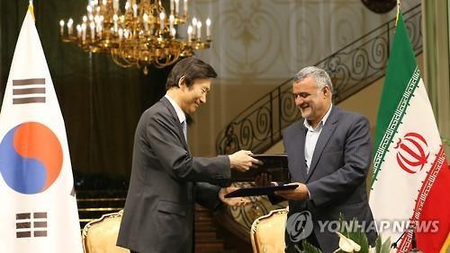 South Korean Foreign Minister Yun Byung-se (left) exchanges documents with Iran's agriculture minister after they signed an MOU on bilateral fisheries business cooperation in Tehran on May 2. (Yonhap)