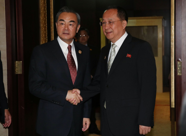 Chinese Foreign Minister Wang Yi (left) shakes hands with North Korean Foreign Minster Ri Yong-ho in Vientiane, Laos, Monday. Yonhap