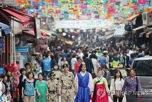 Foreigners -- some wearing traditional Korean clothing, others military uniforms -- take part in the 2016 Namdaemun Market Global Festival that opened at the market in downtown Seoul on May 26 for a three-day run. The festival gives visitors a chance to experience both traditional and modern Korean culture. (Yonhap)