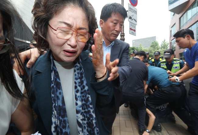 Kim Tae-hyeon, professor emeritus in social welfare studies at Sungshin Women's University, exits the event as one of the protesters threw a capsaicin powder at her face. (yonhap)