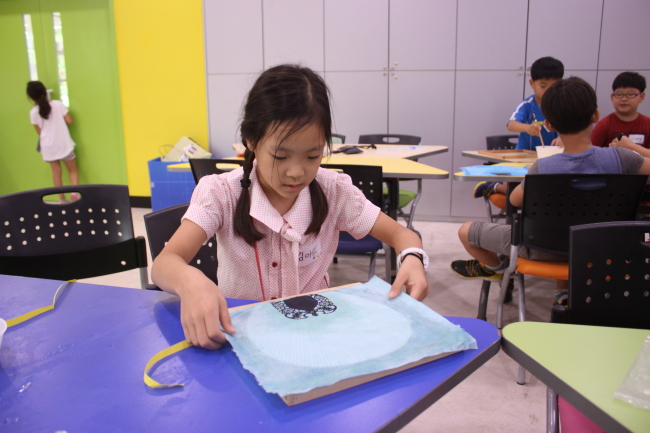 A child makes a fan using traditional mulberry paper at the National Folk Museum of Korea. (National Folk Museum of Korea)