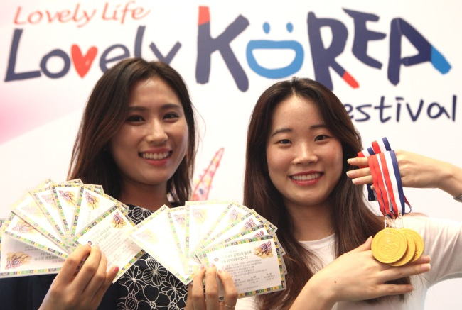 "Models pose with gold medals to promote a giveaway event dubbed ""Lovely Korea Festival"" at the Lotte Department Store headquarters in Sogong-dong, central Seoul. (Yonhap)"
