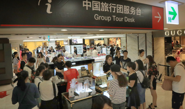 This Aug. 1 photo shows Chinese tourists purchasing Korean cosmetics products at Lotte Duty Free Store in Myeongdong, central Seoul. (Yonhap)