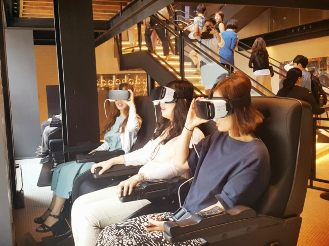 Visitors, sitting in a motion seat, ride a virtual reality roller coaster with Samsung Electronics' Gear VR headset. (Kim Young-won/The Investor)