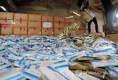 An official from the Korea Customs Service shows a pile of smuggled cigarettes at an office in Busan on Aug. 9. (Yonhap)