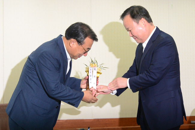 New Saenuri Party leader Rep. Lee Jung-hyun (left) receives a congratulatory orchid from Senior Presidential Secretary for Political Affairs Kim Jae-won at the party's headquarters on Wednesday. (Yonhap)
