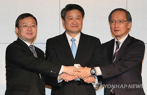 Photo dated May 12, 2015, shows Deputy Foreign Affairs Minister Yasumasa Nagamine (right) posing for a photo with Chinese Vice Commerce Minister Wang Shouwen (left) and the South Korean Trade, Industry and Energy Ministry's FTA policy director Kim Hak-do during their talks on a trilateral free trade agreement at a Seoul hotel. (Yonhap)