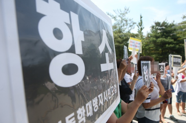 Members of an anti-child abuse organization stage a protest on Aug. 10, calling for strict punishment on parents of Shin Won-young, a seven-year-old who died in February after being severely abused and neglected by his father and stepmother. The stepmother was sentenced to 20 years in jail, while the child's father was sentenced to 15 years behind bars. (Yonhap)