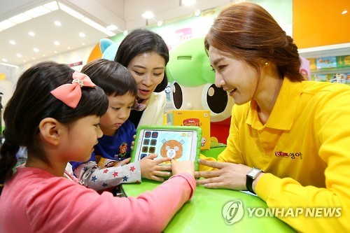 Models demonstrate using an English learning kit during the Educare exhibition in Seoul in April. (Yonhap)