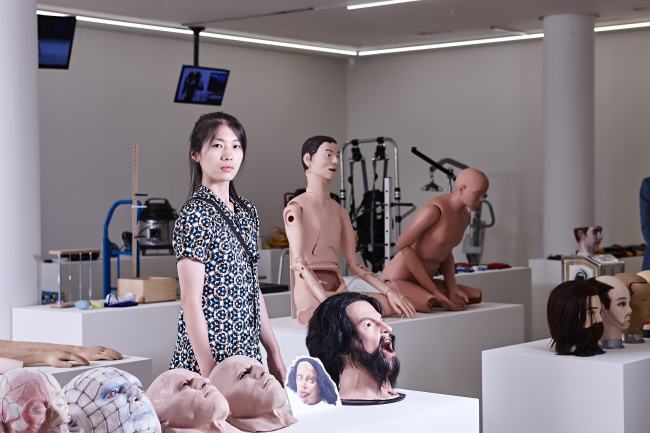 """Artist Jeong Geum-hyung poses with her """"private collection"""" of objects used during her performances. (Nam Ki-yong/Fondation d'entreprise Hermes)"""