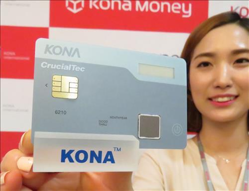 A model poses with a smart card developed by Kona I and fingerprint module maker CrucialTec. The card is equipped with a fingerprint sensor. Kona I