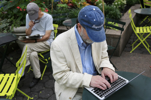 The author and former intelligence official who uses the name James Church in public works on his laptop in a New York park on June 29, 2016. (AP-Yonhap)