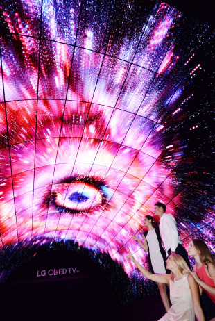 Models pose inside a tunnel illuminated with images from organic light-emitting diode screens. (LG Electronics)