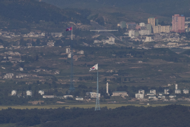The image taken on Aug. 29 from Paju, Gyeonggi Province, shows towns near the inter-Korean border where the South and North Korean flags flap respectively. (Yonhap)
