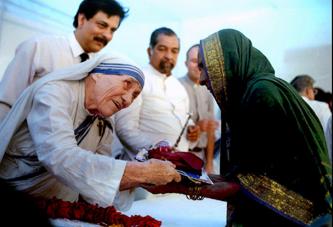 Mother Teresa presents documents for a new house to a villager from Latur in Bombay on Sept. 26, 1994.