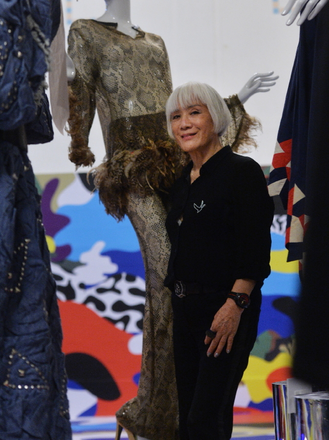 "Fashion designer Troa Cho poses with her work (left) on display at ""Mode & Moments: 100 Years of Korean Fashion"" at the Culture Station Seoul 284 in Seoul, Wednesday. (Yoon Byung-chan/The Korea Herald)"