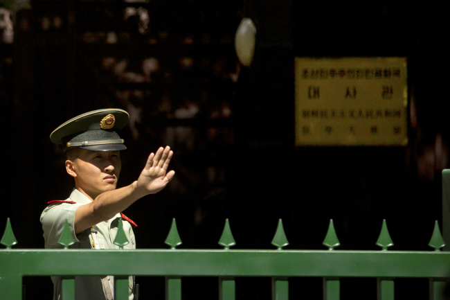 A Chinese police officer holds out a blocking hand from inside the North Korean Ambassy in Beijing on Friday, in the wake of the North's surprise nuclear test. Yonhap
