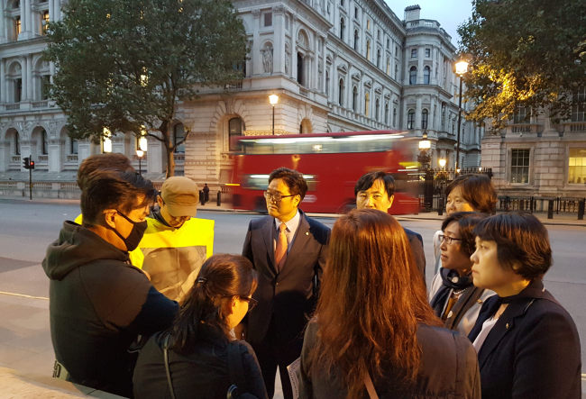 Lawmakers belonging to the special committee on the humidifier disinfectant case talk with families of the victims near the Prime Ministers Office in London on Tuesday. (Yonhap)