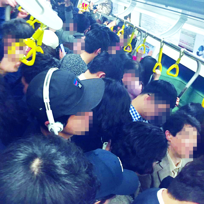 Commuters stand packed inside a Seoul Metro Line 9 train during peak morning hours. (The Korea Herald)