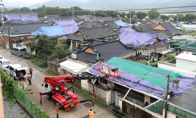 Gyeongju city officials on Sept. 18 work on covering damaged roofs of houses with nets and tents after the area suffered a 5.8 magnitude earthquake the previous week. (Yonhap)