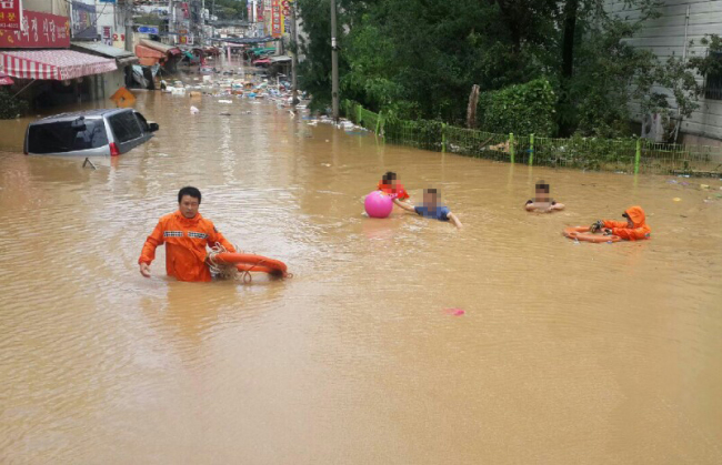 Rescuers are seen shifting through the water in the aftermath of the Typhoon Chaba in Korea (Yonhap)