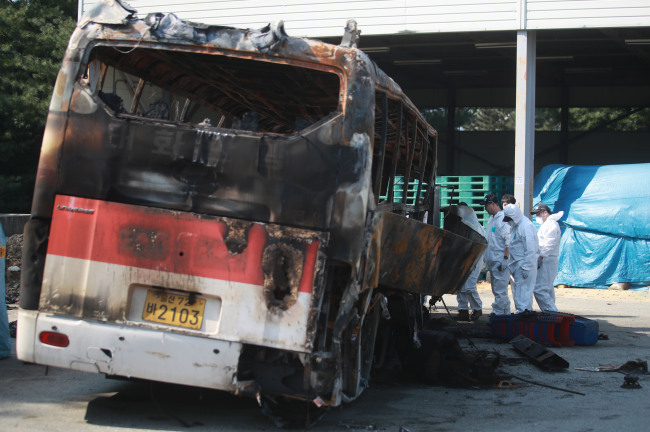 Forensic investigators inspect a tour bus, gutted by fire in a tragic accident that killed 10, in Ulsan on Friday. (Yonhap)