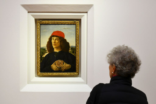 """A woman looks at """"Portrait of a Man with a Medal of Cosimo the Elder"""" painted around 1475 by Italian painter Sandro Botticelli during a press preview for the reopening of the rooms dedicated to Pollaiolo and Botticelli, at the Uffizi Gallery in Florence. (AFP-Yonhap)"""